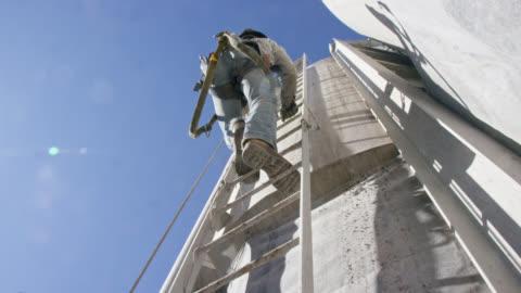 vídeos y material grabado en eventos de stock de un trabajador de oilfield sube una escalera en el lado de un tanque de barro en un sitio de almohadillas de perforación de petróleo y gas en una mañana soleada - equipo de seguridad