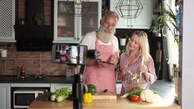 an old bearded man and a young woman have a culinary blog. two persons - facial hair stock videos & royalty-free footage