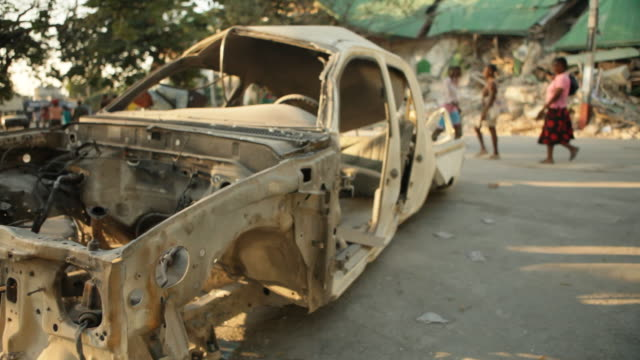 an old body car abandoned in the streets after the haiti earthquake of january 2010 - port au prince stock videos & royalty-free footage
