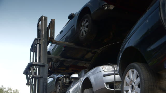 An old car is removed from the top of a stack by a forklift truck at a scrapyard in the UK.