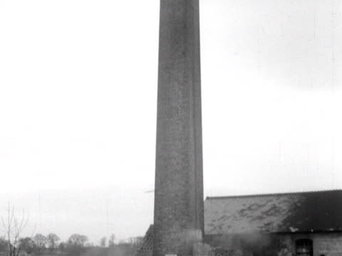 an old colliery chimney is demolished by a controlled explosion - turmarbeiter stock-videos und b-roll-filmmaterial