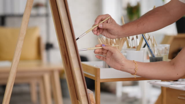 an old couple happily teaches painting at home - mature adult stock videos & royalty-free footage