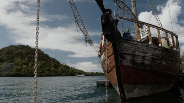 vidéos et rushes de an old historic sailing ship with a pirate flag in the caribbean - french overseas territory