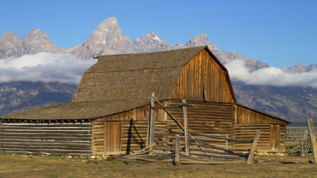 an old homestead barn frames a view of the majestic grand teton mountains in grand teton national park. - grand teton national park bildbanksvideor och videomaterial från bakom kulisserna