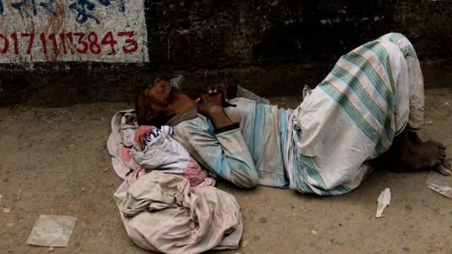 an old man lying on footpath amid coronavirus outbreak in dhaka, bangladesh on march 23, 2020. bangladesh has confirmed 20 cases, with one death due... - senior men stock videos & royalty-free footage