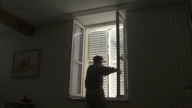 an old man opens shutters on a window. - sash window stock videos and b-roll footage