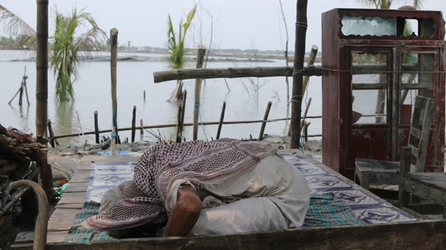 an old man prays in his temporary shelter on the street on june 1, 2021 in khulna, bangladesh. many properties and areas in khulna have been damaged... - praying stock videos & royalty-free footage