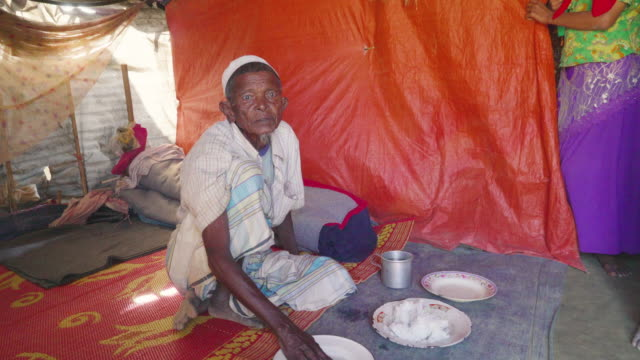 An old man sits in his tent looking at camera and then reaching down to eat his rice in Kutupalong refugee camp Fleeing persecution by the Myanmar...