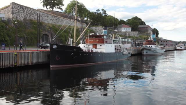 an old ship anchored at the oslo norway harbor near the city castle - anchored stock videos & royalty-free footage