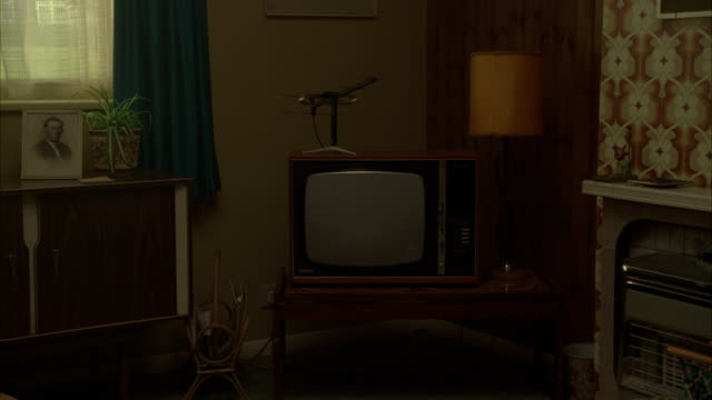 an old television and a dated shelf and lamp  furnish a living room. - the past stock videos & royalty-free footage