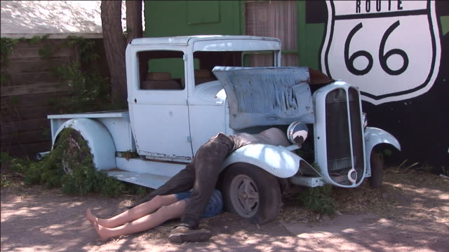 vidéos et rushes de an old truck sits next to a route 66 mural. - route 66