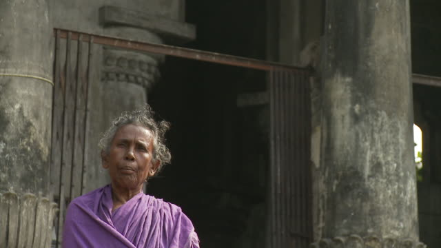 An old woman in a purple sari chews betel nut in front of an old building.