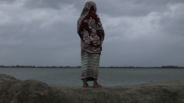 an old woman stands in the embankments during cyclone yass affect bangladesh's coastal area on may 26, 2021. tidal surges and strong winds triggered... - senior women stock videos & royalty-free footage