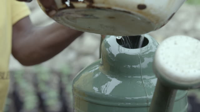 CU of an old woman's hands filling up a watering can