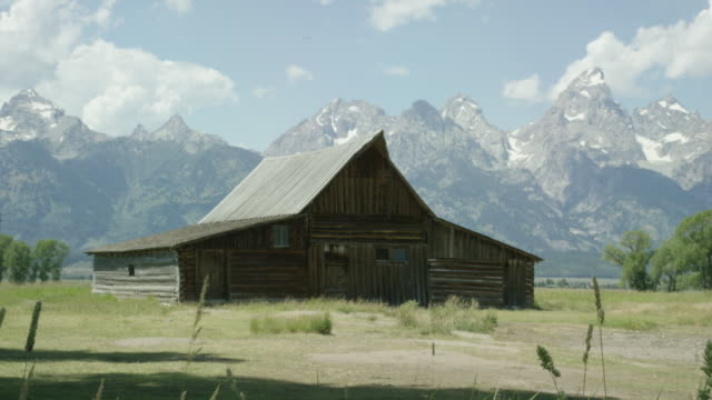 an old wooden cabin/barn sits at the base of the grand teton mountains in grand teton national park in western wyoming on a sunny day - grand teton stock videos & royalty-free footage
