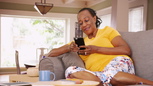vidéos et rushes de an older african american woman uses her mobile phone while sitting on her couch - seniornaute