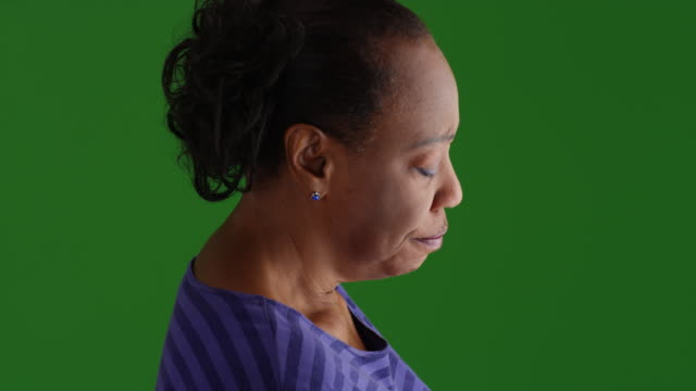 an older black woman mournfully looks out her window on green screen - donne anziane video stock e b–roll