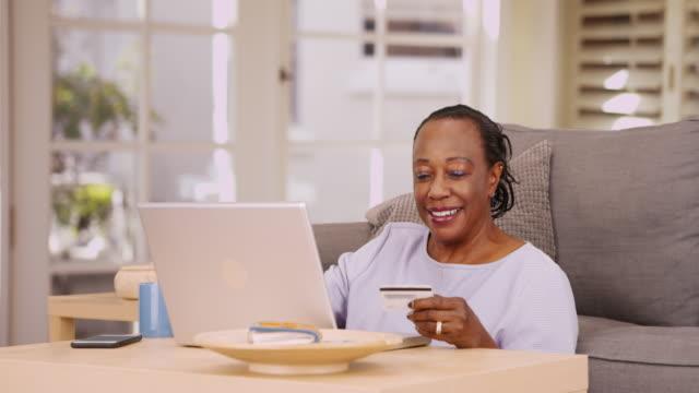 vídeos de stock, filmes e b-roll de an older black woman pays her bills on her laptop - computador desktop