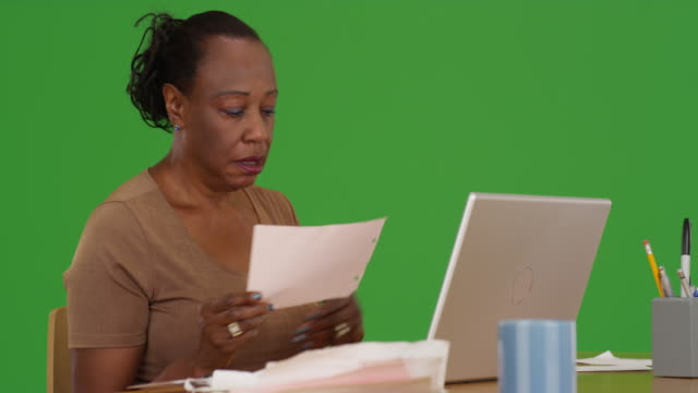 an older black woman uses her phone and laptop to do her taxes on green screen - maestra video stock e b–roll