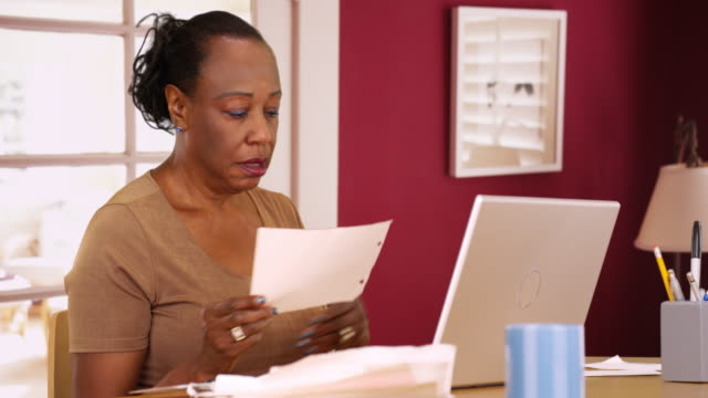 an older black woman uses her phone and laptop to do her taxes - paying taxes stock videos & royalty-free footage