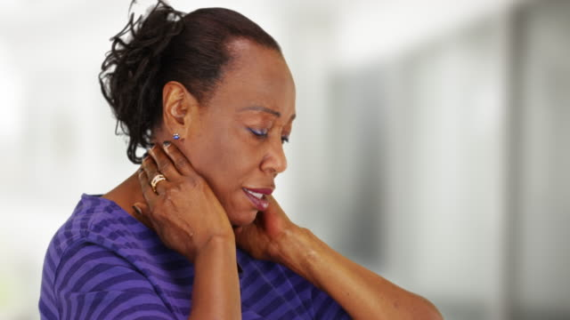 vídeos de stock, filmes e b-roll de an older black woman with bad neck pain - ombro