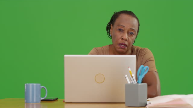 an older black woman working on her laptop in her living room on green screen - maestra video stock e b–roll