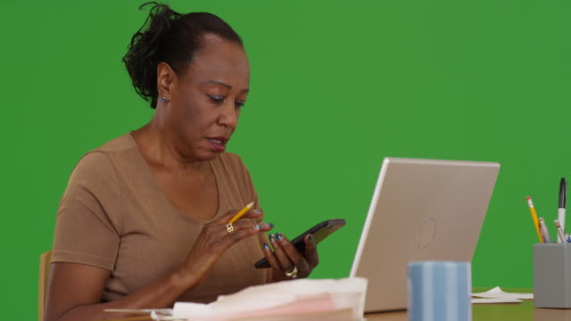an older black woman works on her laptop with her paperwork on green screen - maestra video stock e b–roll