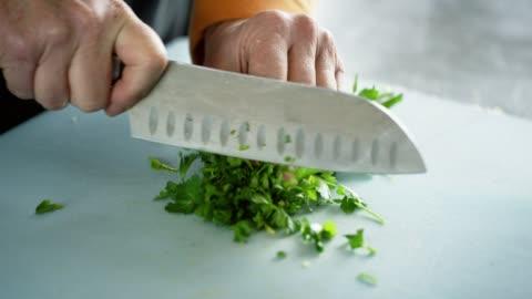 vídeos y material grabado en eventos de stock de una mujer caucásica más vieja chuta cilantro en una tabla de cortar con un cuchillo de cocina - pasatiempos