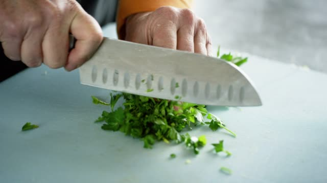 an older caucasian woman chops cilantro on a cutting board with a kitchen knife - parsley stock videos and b-roll footage
