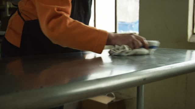 vídeos de stock e filmes b-roll de an older caucasian woman cleans a stainless steel countertop in a commercial kitchen with a dish cloth - limpar