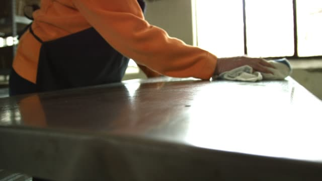 vídeos de stock e filmes b-roll de an older caucasian woman cleans a stainless steel countertop in a commercial kitchen with a dish cloth - gastrónomo