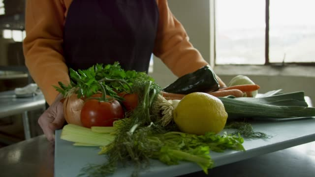 vídeos de stock e filmes b-roll de an older caucasian woman picks up a cutting board filled with vegetables and places it on a a stainless steel countertop in a commercial kitchen - cozinha industrial