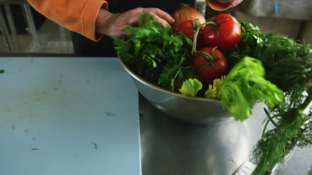 an older caucasian woman picks vegetables up off a cutting board and places them in a metal bowl in a commercial kitchen - ketogenic diet stock videos & royalty-free footage
