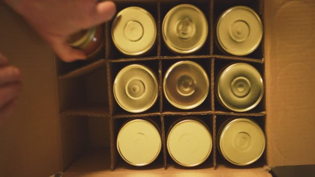 an older caucasian woman places jars of food into a cardboard box for shipping and distribution in a manufacturing facility - canning stock videos & royalty-free footage