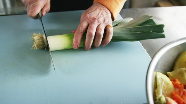 an older caucasian woman slices a leek on a cutting board with a kitchen knife next to a metal bowl full of vegetables in a commercial kitchen - ketogenic diet stock videos & royalty-free footage