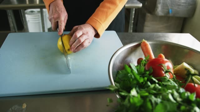 an older caucasian woman slices a lemon on a cutting board with a kitchen knife next to a metal bowl filled with vegetables in a commercial kitchen - ketogenic diet stock videos & royalty-free footage