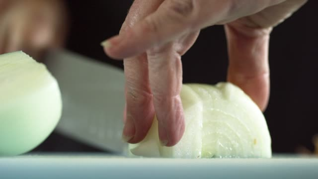 an older caucasian woman slices an onion on a cutting board with a kitchen knife - onion stock videos & royalty-free footage