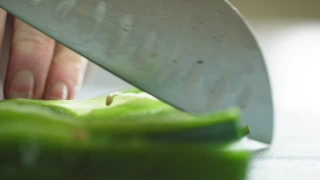 an older caucasian woman slices and chops a poblano pepper on a cutting board with a kitchen knife - pepper vegetable stock videos and b-roll footage