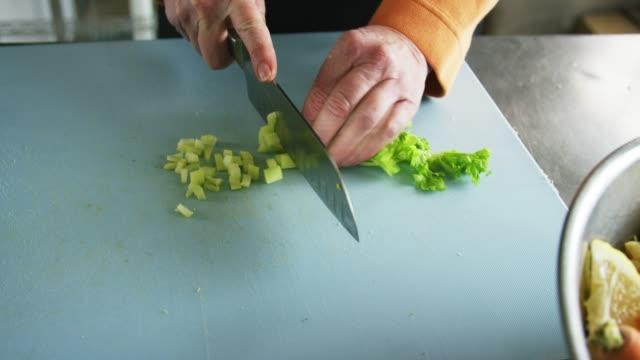 vídeos de stock, filmes e b-roll de uma mulher caucasiano mais idosa corta o aipo em uma placa de estaca com uma faca de cozinha em uma cozinha comercial - aipo