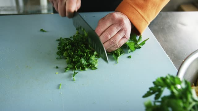 an older caucasian woman slices parsley on a cutting board with a kitchen knife in a commercial kitchen - parsley stock videos and b-roll footage