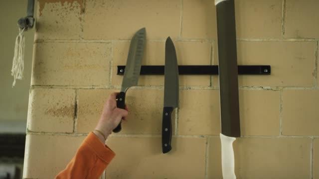 vídeos de stock, filmes e b-roll de a mão de uma mulher caucasiano mais idosa agarra uma faca de cozinha de uma tira magnética que prenda outros utensílios em uma cozinha comercial - faqueiro