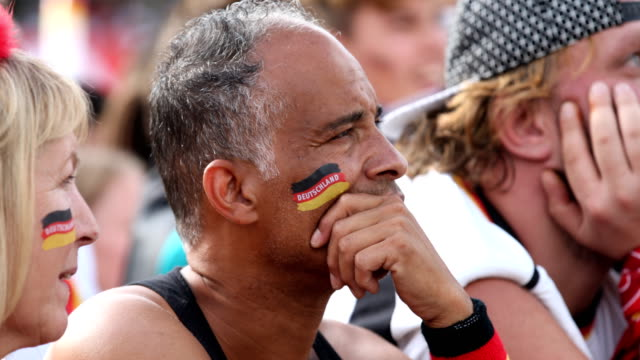 An older football fan with a German flag on his cheeks is critically watching the game and is disappointed while Germany is loosing the 2018 FIFA...