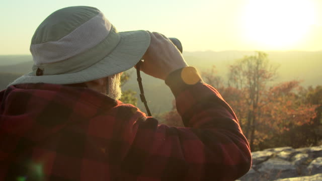 An older hiker looking through binoculars while on a scenic hike in the mountains.