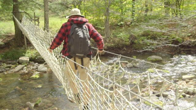 vídeos de stock e filmes b-roll de an older man crossing a rope bridge over a creek while on a scenic hike in the mountains. - ponte suspensa