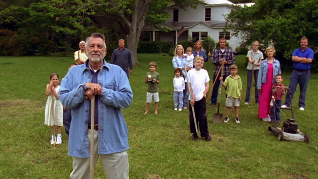 an older man stands in front of a group of neighbors in a backyard. - wilmington north carolina stock-videos und b-roll-filmmaterial