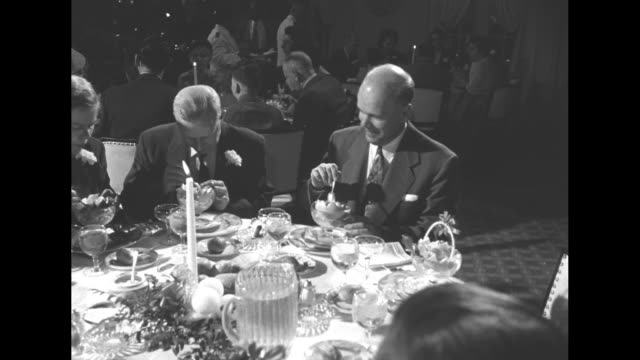 An older man wearing sunglasses and a boutonniere with a woman and girl at a banquet table with sign The Musicians Christmas Party at rear / an older...