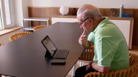 vídeos de stock, filmes e b-roll de an older man working and watching on a tablet with keyboard on a table - presidente de empresa