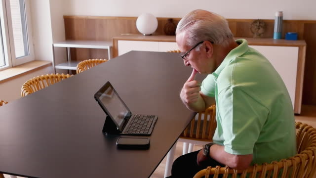 an older man working and watching on a tablet with keyboard on a table - chairperson stock videos & royalty-free footage