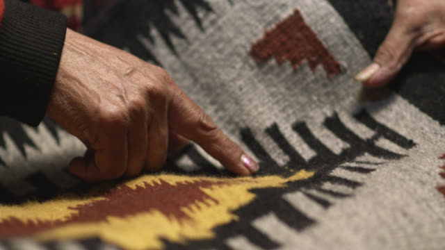vídeos de stock e filmes b-roll de an older native american (navajo) woman's hand's point to designs on a navajo blanket while a younger girl watches - cultura tribal da américa do norte