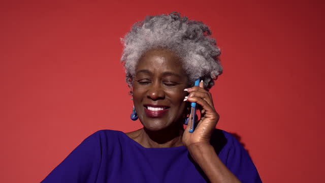 an older woman in blue talks on the phone - multi coloured stock videos & royalty-free footage